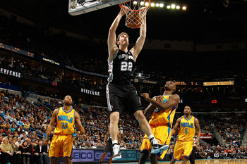 NEW ORLEANS, LA - JANUARY 22:  Tiago Splitter #22 of the San Antonio Spurs dunks the ball over Emeka Okafor #50 of the New Orleans Hornets at the New Orleans Arena on January 22, 2011 in New Orleans, Louisiana.  The Hornets defeated the Spurs 96-72.  NOTE