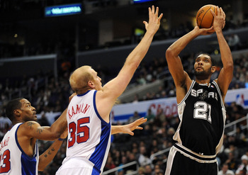 LOS ANGELES, CA - DECEMBER 13:  Tim Duncan #21 of the San Antonio Spurs shoots a jumper over Chris Kaman #35 and Marcus Camby #23 of the Los Angeles Clippers during the game at Staples Center on December 13, 2009 in Los Angeles, California.  NOTE TO USER: