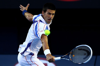 MELBOURNE, AUSTRALIA - JANUARY 27:  Novak Djokovic of Serbia plays a backhand in his semifinal match against Roger Federer of Switzerland during day eleven of the 2011 Australian Open at Melbourne Park on January 27, 2011 in Melbourne, Australia.  (Photo