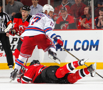 NEWARK, NJ - FEBRUARY 18:  Brandon Dubinsky #17 of the New York Rangers has to step over Ilya Kovalchuk #17 of the New Jersey Devils as he slides on the ice during the third period of an NHL hockey game at the Prudential Center on February 18, 2011 in New