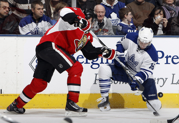TORONTO, CANADA - FEBRUARY 19: Clarke MacArthur #16 of the Toronto Maple Leafs blocks the shot of Chris Phillips #4 of the Ottawa Senators at the Air Canada Centre February 19, 2011 in Toronto, Ontario, Canada. (Photo by Abelimages/Getty Images)