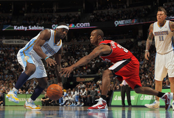 DENVER - DECEMBER 28:  Ty Lawson #3 of the Denver Nuggets dribbles the ball against Dante Cunningham #33 of the Portland Trail Blazers at Pepsi Center on December 28, 2010 in Denver, Colorado. The Nuggets defeated the Blazers 95-77. NOTE TO USER: User exp