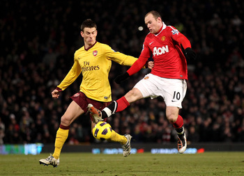 MANCHESTER, ENGLAND - DECEMBER 13:  Wayne Rooney of Manchester United tangles with Laurent Koscielny of Arsenal during the Barclays Premier League match between Manchester United and Arsenal at Old Trafford on December 13, 2010 in Manchester, England.  (P