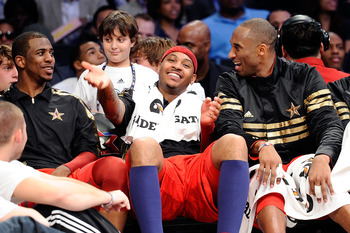 LOS ANGELES, CA - FEBRUARY 20:  (M) Carmelo Anthony #15 of the Denver Nuggets and the Western Conference reacts as he sits between Chris Paul #3 of the New Orleans Hornets and the Western Conference and Kobe Bryant #24 of the Los Angeles Lakers and the We