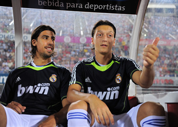 PALMA DE MALLORCA, SPAIN - AUGUST 29:  Mesut Ozil (R) of Real Madrid jokes while seated on the bench flanked by his teammate and fellow countryman Sami Khedira during the La Liga match between Mallorca and Real Madrid at the ONO Estadio on August 29, 2010