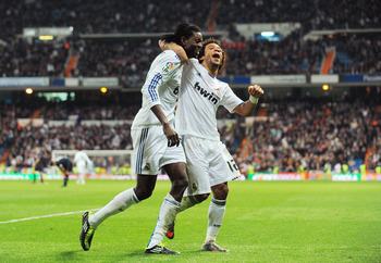 MADRID, SPAIN - FEBRUARY 06:  Emmanuel Adebayor (L) of Real Madrid celebrates with Marcelo after scoring Real's fourth goal during the La Liga match between Real Madrid and Real Sociedad at Estadio Santiago Bernabeu on February 6, 2011 in Madrid, Spain.