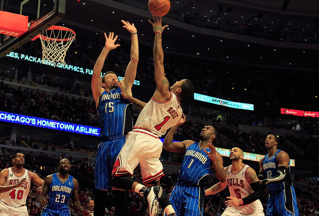 CHICAGO, IL - JANUARY 28: Derrick Rose #1 of the Chicago Bulls puts up a shot between Hedo Turkoglu #15 and Gilbert Arenas #1 of the Orlando Magic at the United Center on January 28, 2011 in Chicago, Illinois. The Bulls defeated the Magic 99-90. NOTE TO U