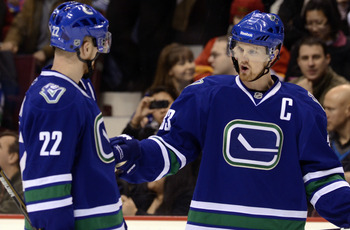 VANCOUVER, CANADA - FEBRUARY 12:  Brothers Daniel Sedin #22 and Henrik Sedin #33 of the Vancouver Canucks talk during a break in in NHL action against the Calgary Flames on February 12, 2011 at Rogers Arena in Vancouver, British Columbia, Canada.  (Photo