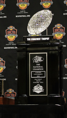 SCOTTSDALE, AZ - JANUARY 11:  Head coach Gene Chizik of the Auburn Tigers stands with the (L-R) Associated Press, Football Writers of America, MacArthur Bowl and the Coaches trophys during a press conference for the Tostitos BCS National Championship Game