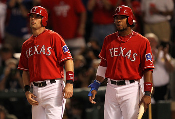 ARLINGTON, TX - OCTOBER 15:  Elvis Andrus #1 (R) and Michael Young #10 of the Texas Rangers wait for Josh Hamilton after they scored on Hamilton's 3-run home run in the first inning against the New York Yankees in Game One of the ALCS during the 2010 MLB