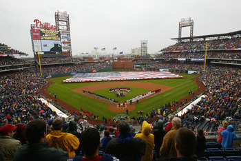 PHILADELPHIA - APRIL 12:  Military personel adorn the outfield with an American flag as the Philadelphia city skyline provides a back drop during opening ceremonies as the Philadelphia Phillies host the Cincinnati Reds during MLB action at the inaugural g