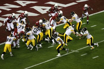 TAMPA, FL - FEBRUARY 01:  Ben Roethlisberger #7 of the Pittsburgh Steelers hands the ball off to Gary Russell #33 against the Arizona Cardinals during Super Bowl XLIII on February 1, 2009 at Raymond James Stadium in Tampa, Florida.  (Photo by Doug Benc/Ge