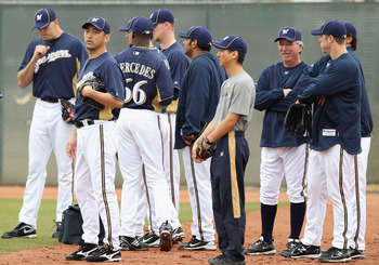 PHOENIX, AZ - FEBRUARY 18:  Pitcher Takashi Saito #40 (2nd from left) of the Milwaukee Brewers warms up with teammates during a MLB spring training practice at Maryvale Baseball Park on February 18, 2011 in Phoenix, Arizona.  (Photo by Christian Petersen/