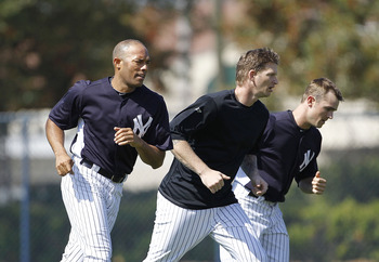 TAMPA, FL - FEBRUARY 21: Mariano Rivera #42, A J Burnett #34, and David Robertson #30 of the New York Yankees work out during the second day of full teams workouts at Spring Training on February 21, 2011 at the George M. Steinbrenner Field in Tampa, Flori