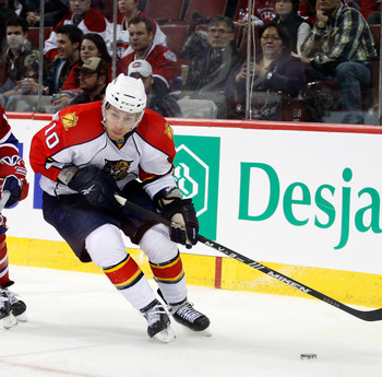 MONTREAL, CANADA - FEBRUARY 2:  David Booth #10 of the Florida Panthers skates with the puck while being chased by Jeff Halpern #15 of the Montreal Canadiens during the NHL game at the Bell Centre on February 2, 2011 in Montreal, Quebec, Canada.  The Cana
