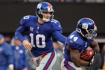 EAST RUTHERFORD, NJ - DECEMBER 05:  Eli Manning #10 of the New York Giants hands the ball off to teammate Ahmad Bradshaw #44 against the Washington Redskins on December 5, 2010 at the New Meadowlands Stadium in East Rutherford, New Jersey. The Giants defe