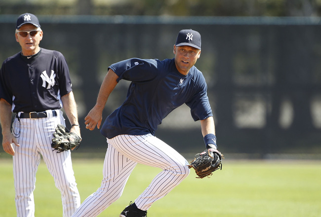 TAMPA, FL - FEBRUARY 21:  Derek Jeter #2 of the New York Yankees breaks for a ground ball as Mick Kelleher #50 looks on during the second day of full teams workouts at Spring Training on February 21, 2011 at the George M. Steinbrenner Field in Tampa, Flor