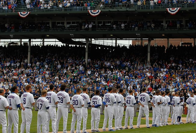 CHICAGO - APRIL 12: Members of the Chicago Cubs and the Milwaukee Brewers stand for the National Anthem on Opening Day at Wrigley Field on April 12, 2010 in Chicago, Illinois. (Photo by Jonathan Daniel/Getty Images)