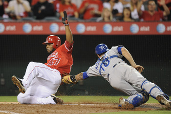 ANAHEIM, CA - AUGUST 10:  Howie Kendrick #47 of the Los Angeles Angels scores a run off of a squeeze play past Jason Kendall #18 of the Kansas City Royals for a 2-1 lead during the fifth inning at Angel Stadium on August 10, 2010 in Anaheim, California.