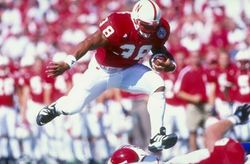 23 Aug 1998: Dan Alexander #38 of the Nebraska Cornhuskers grips the ball as he leaps over players during the  Eddie Robison Classic game against the Louisiana  Tech Bulldogs at Tom Osborne Field in Lincoln, Nebraska. Nebraska defeated Louisiana Tech 56-2