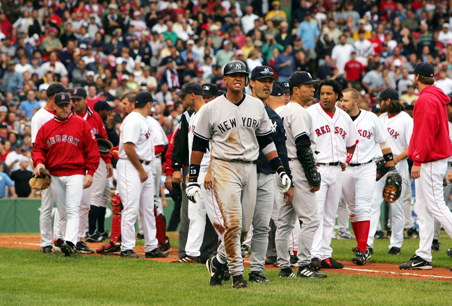 BOSTON - JULY 24:  Alex Rodriguez #13 of the New York Yankees walks to first base with hitting coach Don Mattingly #23 after a fight with Jason Varitek #33 of the Boston Red Sox in the third inning after Rodriguez was hit by a pitch by pitcher Bronson Arr