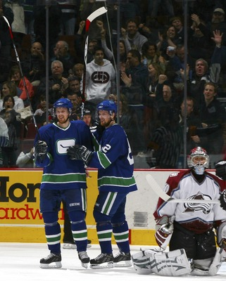 VANCOUVER, CANADA - FEBRUARY 18:   Henrik Sedin #33 (left) and Daniel Sedin #22 of the Vancouver Canucks celebrate Henrik's goal as Jose Theodore #60 of the Colorado Avalanche sits alongside in the crease during their game at General Motors Place on Febru