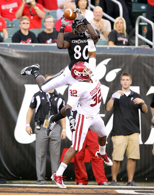CINCINNATI - SEPTEMBER 25:   Armon Binns #80 of the Cincinnati Bearcats reaches up for a pass while defended by Jamell Fleming #32 of the Oklahoma Sooners during the game at Paul Brown Stadium on September 25, 2010 in Cincinnati, Ohio. The pass in the end