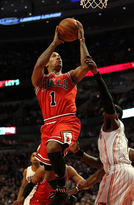 CHICAGO, IL - FEBRUARY 15: Derrick Rose #1 of the Chicago Bulls goes up to shoot past Stephen Jackson #1 of the Charlotte Bobcats at the United Center on February 15, 2011 in Chicago, Illinois. The Bulls defeated the Bobcats 106-94. NOTE TO USER: User exp