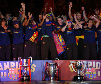 BARCELONA, SPAIN - MAY 28: Barcelona players celebrate beside their three thophys, Copa del Rey (L), UEFA Champions League and La Liga at the Nou Camp Stadium the day after Barcelona won the UEFA Champions League Cup final on May 28, 2009 in Barcelona, Sp