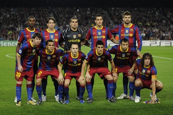 BARCELONA, SPAIN - OCTOBER 20:  Barcelona players (From L-R) Eric Abidal, Lionell Messi, Maxwell, Daniel Alves, Jose Pinto, Andres Iniesta, David Villa, Sergio Busquets, Javier Mascherano, Gerard Pique, Carles Puyol pose for a team picture during the UEFA
