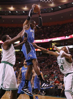 BOSTON, MA - FEBRUARY 06:  Dwight Howard #12 of the Orlando Magic grabs the rebound before Kendrick Perkins #43 and Paul Pierce #34 of the Boston Celtics on February 6, 2011 at the TD Garden in Boston, Massachusetts. The Celtics defeated the Magic 91-80.