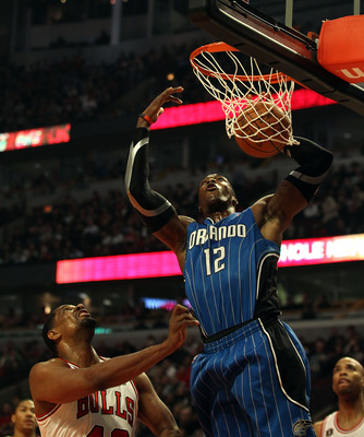 CHICAGO, IL - JANUARY 28: Dwight Howard #12 of the Orlando Magic dunks the ball over Kurt Thomas #40 of the Chicago Bulls at the United Center on January 28, 2011 in Chicago, Illinois. NOTE TO USER: User expressly acknowledges and agrees that, by download