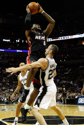 SAN ANTONIO - OCTOBER 09:  LeBron James #6 of the Miami Heat makes a shot over Manu Ginobili #20 of the San Antonio Spurs at the AT&T Center on October 9, 2010 in San Antonio, Texas.  NOTE TO USER: User expressly acknowledges and agrees that, by downloadi