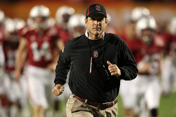 MIAMI, FL - JANUARY 03:  Head coach Jim Harbaugh of the Stanford Cardinal runs on the field during warm ups against the Virginai Tech Hokies during the 2011 Discover Orange Bowl at Sun Life Stadium on January 3, 2011 in Miami, Florida.  (Photo by Streeter