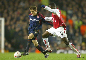 LONDON - JANUARY 20:  Juninho of Middlesbrough is challenged by Kolo Toure of Arsenal during the Carling Cup Semi-Final first leg match between Arsenal and Middlesbrough on January 20, 2004 at Highbury in London, England.  (Photo by Phil Cole/Getty Images