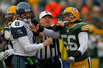 GREEN BAY, WI - DECEMBER 27: Referee Walt Coleman #65 breaks up an altercation between Nick Barnett #56 of the Green Bay Packers and Matt Hesselbeck #8 of the Seattle Seahawks at Lambeau Field on December 27, 2009 in Green Bay, Wisconsin. (Photo by Jonath