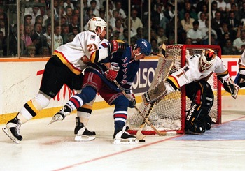 7 Jun 1994: RANGERS FORWARD STEVE LARMER IS MANHANDLED BY CANUCKS DEFENSEMAN JYRKI LUMME WHILE GOALTENDER KIRK MCLEAN POKE-CHECKS AWAY THE PUCK DURING THE THIRD OF GAME FOUR OF THE STANLEY CUP FINALS IN VANCOUVER, BRITISH COLUMBIA. LUMME WAS CALLED FOR A