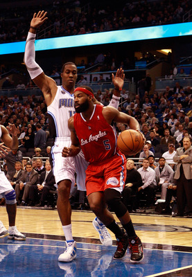 ORLANDO, FL - FEBRUARY 08:  Baron Davis #5 of the Los Angeles Clippers is guarded by Dwight Howard #12 of the Orlando Magic during the game at Amway Arena on February 8, 2011 in Orlando, Florida.  NOTE TO USER: User expressly acknowledges and agrees that,