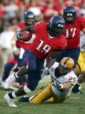 TUCSON, AZ - NOVEMBER 25:  Chris Henry #19 of the Arizona Wildcats runs with the ball as Mike Nixon #25 of the Arizona State Sun Devils tries to block him in the first half of the game at Arizona Stadium on November 25, 2006 in Tucson, Arizona.  (Photo by