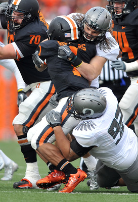 CORVALLIS, OR - DECEMBER 4: Jacquizz Rodgers #1 of the Oregon State Beavers is wrapped up by Casey Matthews #55 and Wade Keliikipi #92 of the Oregon Ducks in the first quarter of the game at Reser Stadium on December 4, 2010 in Corvallis, Oregon. The Duck