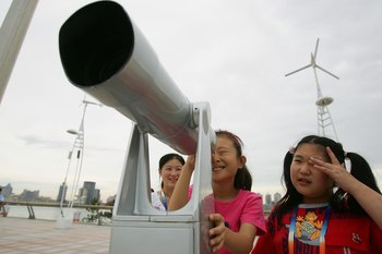 QINGDAO, SHANDONG - AUGUST 26:  Chinese children watch the competition with a telescope at the race observation area of the Qingdao Olympic Sailing Center during the 2006 Qingdao International Regatta, which is the first official test event for the 2008 B