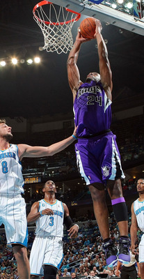 NEW ORLEANS, LA - DECEMBER 15:  Carl Landry #24 of the Sacramento Kings dunks the ball over Marco Belinelli #8 of the New Orleans Hornets  at the New Orleans Arena on December 15, 2010 in New Orleans, Louisiana.  NOTE TO USER: User expressly acknowledges