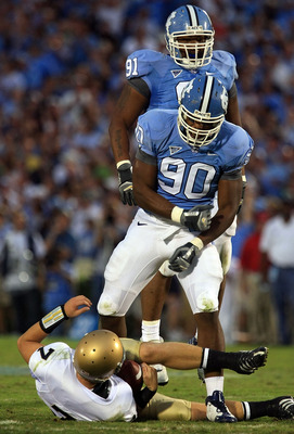 CHAPEL HILL, NC - OCTOBER 11:  Quinton Coples #90 and Tydreke Powell #91 of the North Carolina Tar Heels celebrates after sacking Jimmy Clauson #7 of the Notre Dame Fighting Irish at Kenan Stadium October 11, 2008 in Chapel Hill, North Carolina.  (Photo b