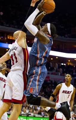 CHARLOTTE, NC - FEBRUARY 04:  Gerald Wallace #3 of the Charlotte Bobcats shoots over Zydrunas Ilgauskus #11 of the Miami Heat at the Time Warner Cable Arena on February 4, 2011 in Charlotte, North Carolina.  The Heat defeated the Bobcats 109-97.  NOTE TO