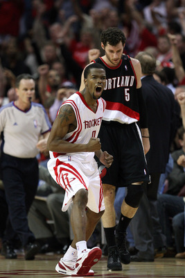 HOUSTON - APRIL 30:  Guard Aaron Brooks #0 of the Houston Rockets reacts after making a three-point shot in front of Rudy Fernandez #5 of the Portland Trail Blazers in Game Six of the Western Conference Quarterfinals during the 2009 NBA Playoffs at Toyota