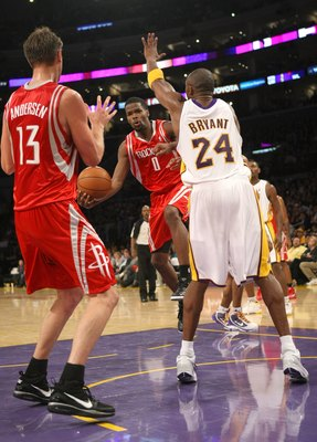 LOS ANGELES, CA - NOVEMBER 15:  Aaron Brooks #0 of the Houston Rockets passes the ball to David Andersen #13 in front of Kobe Bryant #24 of the Los Angeles Lakers on November 15, 2009 at Staples Center in Los Angeles, California.  The Rockets won 101-91.