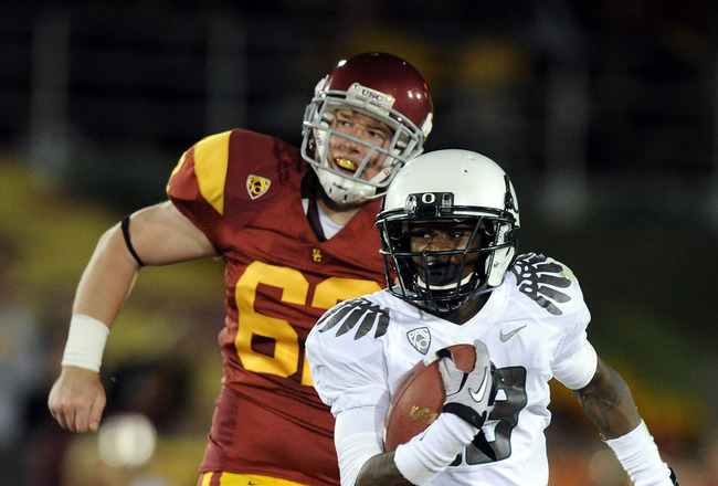 LOS ANGELES, CA - OCTOBER 30:  Cliff Harris #13 of the Oregon Ducks runs past Chris Pousson #62 of the USC Trojans during the second quarter at Los Angeles Memorial Coliseum on October 30, 2010 in Los Angeles, California.  (Photo by Harry How/Getty Images