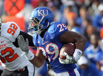 LAWRENCE, KS - NOVEMBER 20:  Running back James Sims #29 of the Kansas Jayhawks carries the ball as Darius Hart #92 of the Oklahoma State Cowboys defends during the game on November 20, 2010 at Memorial Stadium in Lawrence, Kansas.  (Photo by Jamie Squire