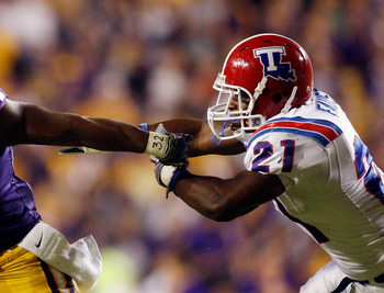 BATON ROUGE, LA - NOVEMBER 14:  Stevan Ridley #34 of the LSU Tigers  avoids a tackle by Dominique Faust #21 of the Louisiana Tech Bulldogs at Tiger Stadium on November 14, 2009 in Baton Rouge, Louisiana.  The Tigers defeated the Bulldogs 24-16.  (Photo by