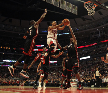 CHICAGO, IL - FEBRUARY 24: Derrick Rose #1 of the Chicago Bulls puts up a shot between Dwyane Wade #3 and Chris Bosh #1 of the Miami Heat at the United Center on February 24, 2011 in Chicago, Illinois. The Bulls defeated the Heat 93-89. NOTE TO USER: User
